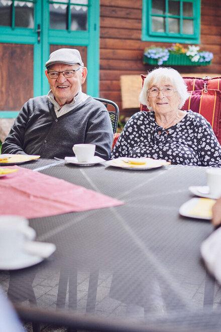 Ein älteres Paar sitzt an einem Tisch im Garten und lächeln