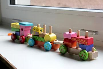 Kleine bunte Holzeisenbahn mit Holzsteinchen zum Herausnehmen.