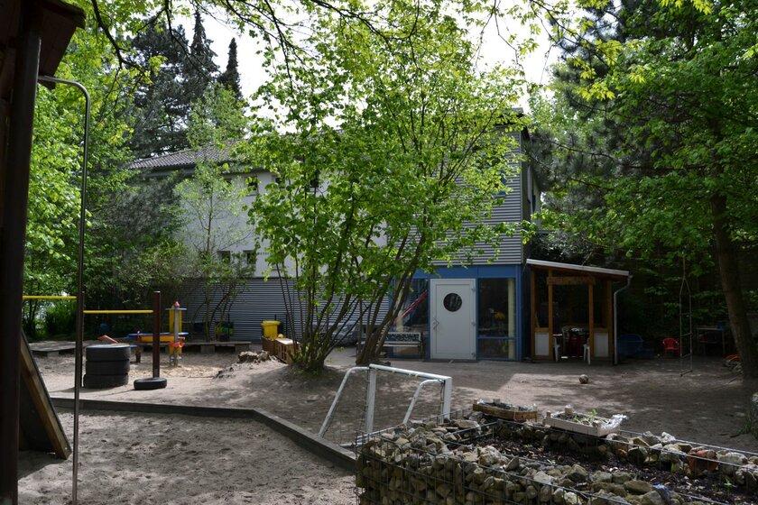 Vor dem Kitagebäude gibt es Sand, Bäume, ein kleines Fußballtor und Hochbeete mit Kräutern.