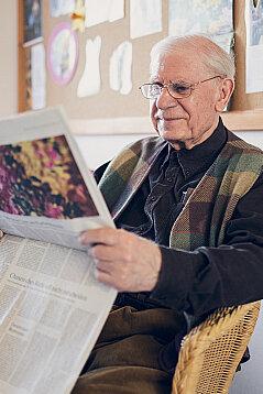 Ein älterer Herr liest in der Tageszeitung