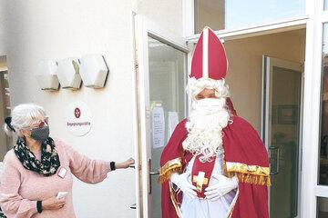 Eine grauhaarige Frau mit einem Mundnasenschutz öffnet einem als Nikolaus verkleideten Mann die Tür.