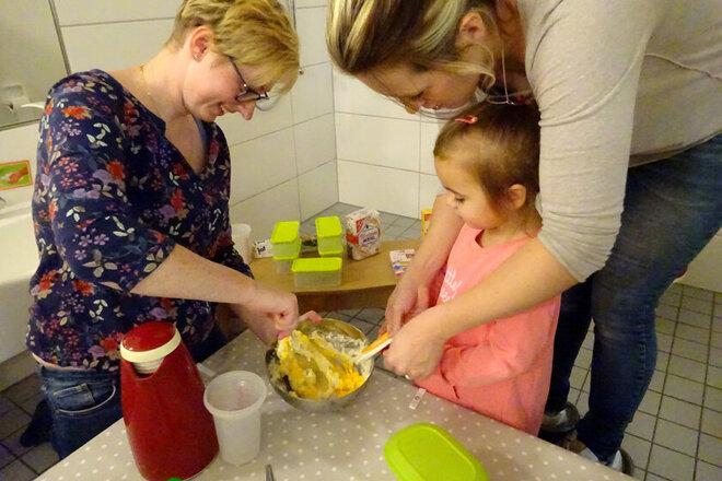 Erzieherin, Mutter und Kita-Kind machen gemeinsam Kürbis-Kartoffel-Püree.