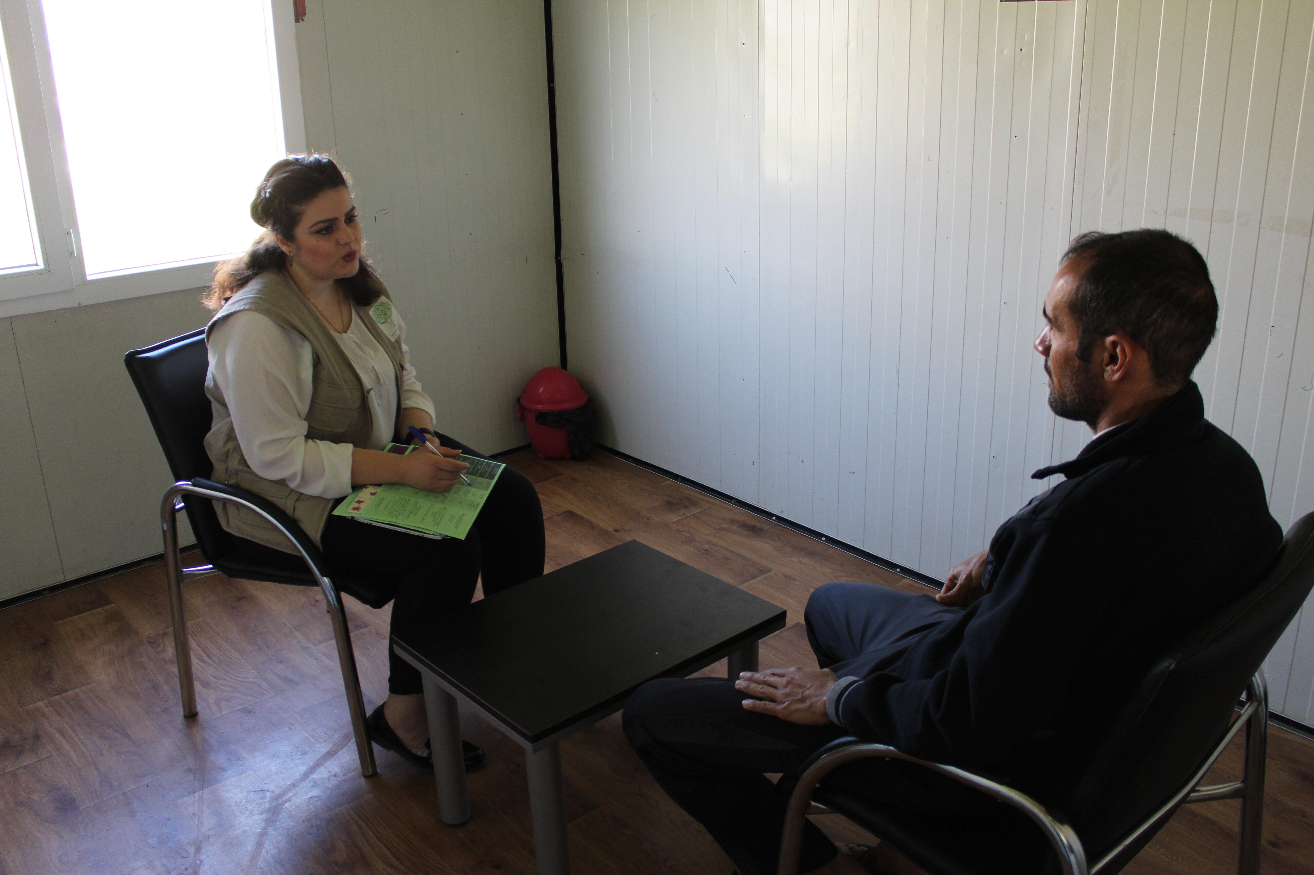Eine Jiyan-Mitarbeiterin im Gespräch mit einem Patienten