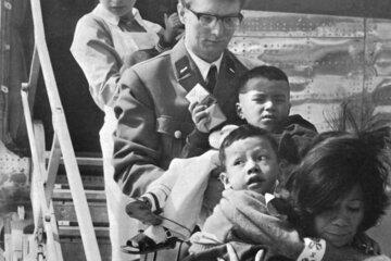 Helferinnen und Helfer nehmen im Jahr 1970 auf dem Hamburger Flughafen verletzte Kinder aus Vietnam in Empfang.