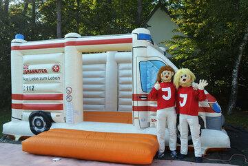 Eine Hüpfburg in Form eines Rettungswagnes mit zwei als Figuren verkleidete Menschen, die in die Kamera winken