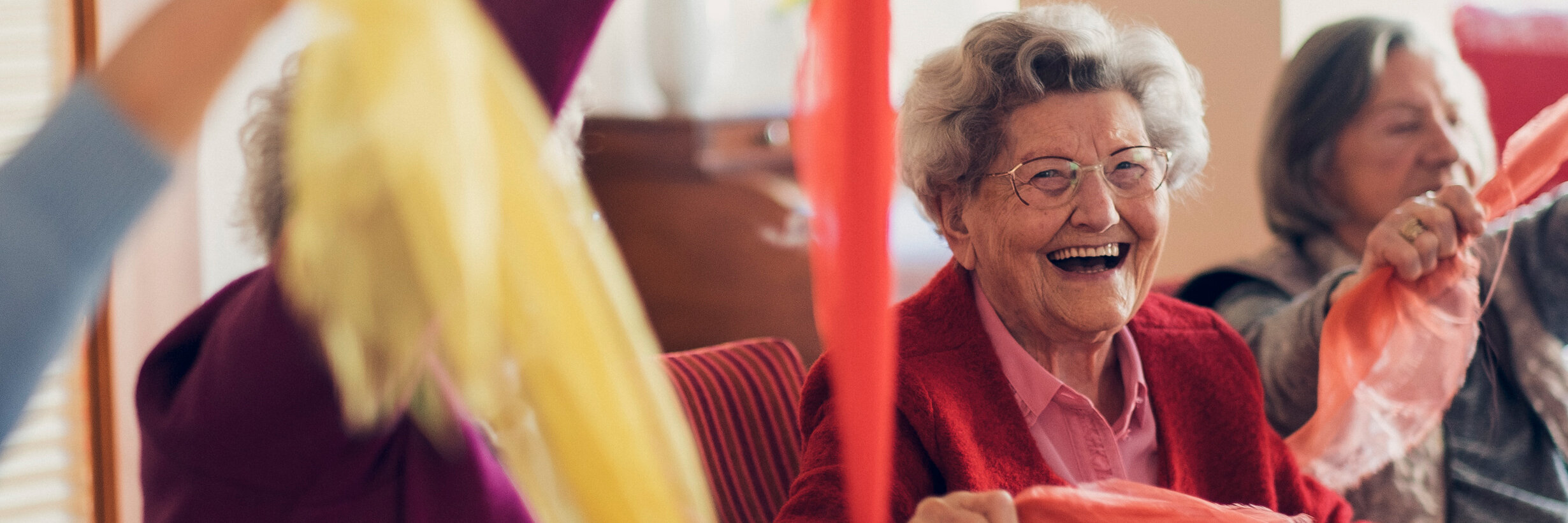 Lachende auf dem Stuhl sitzende Seniorinnen bewegen sich spielend mit einem bunten Tuch