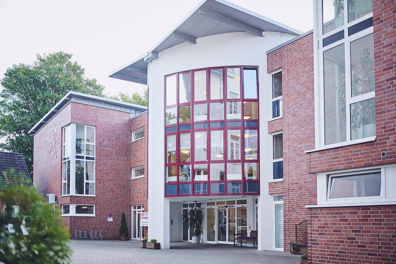 Der Haupteingang befindet sich in der Mitte des Hauses mit großen Fenstern und geschwungenen Dach