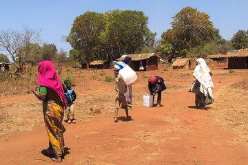 Frauen die Wasserkanister tragen
