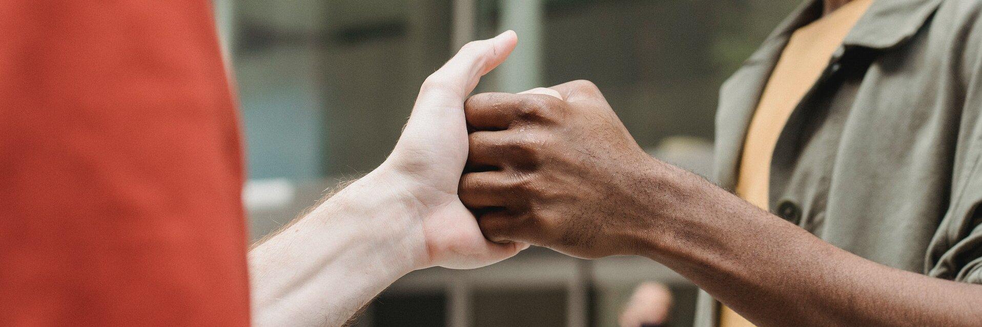 Zwei Menschen geben sich die Hand.