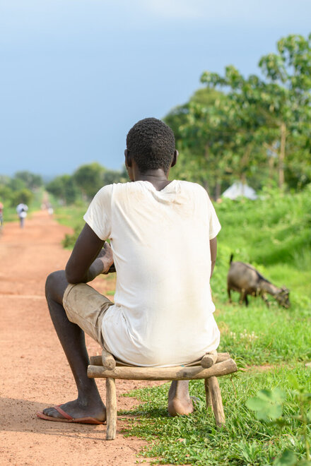 Lomuju is sitting on a chair, looking on the long road in front of him.