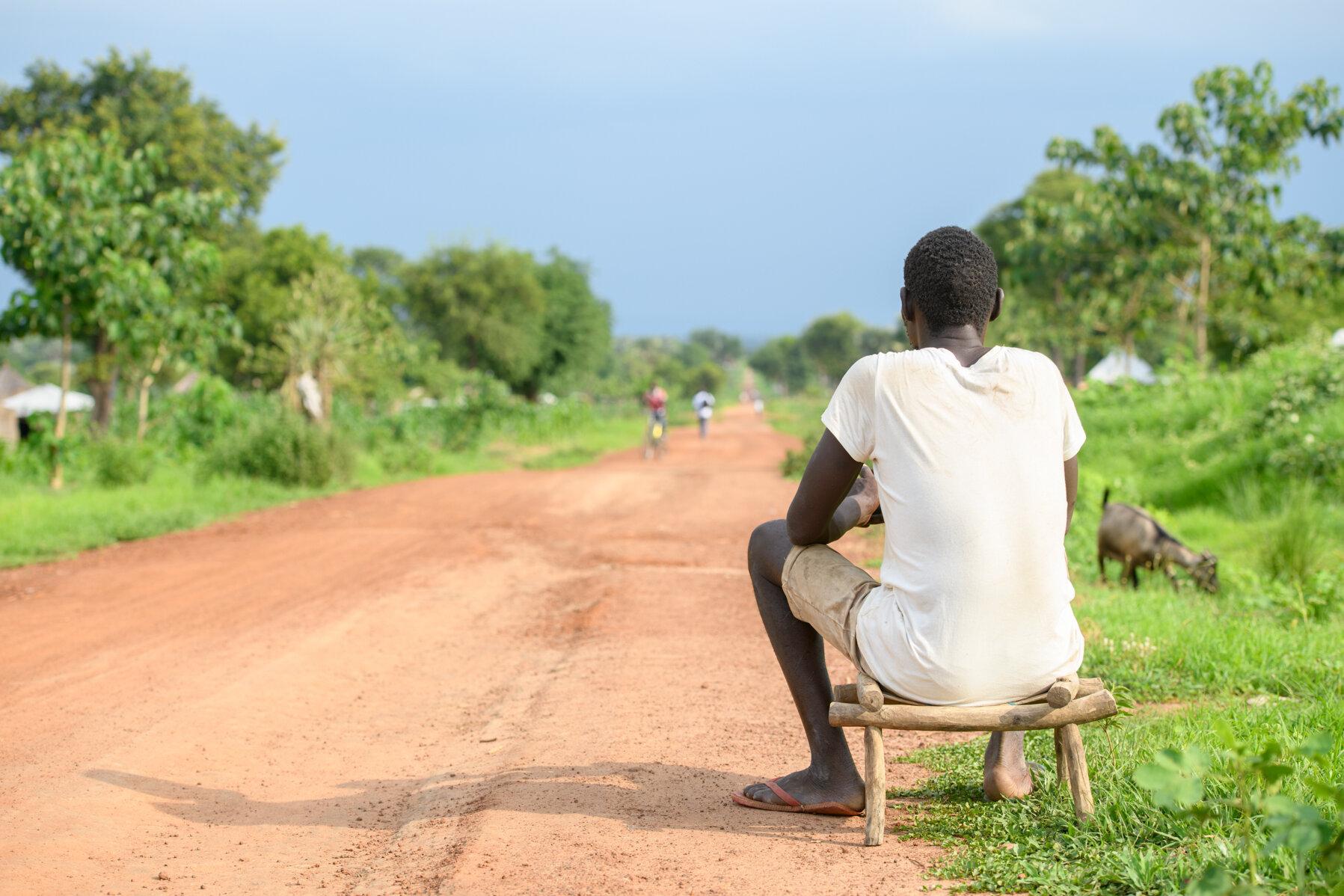 Lomuju sitzt auf einem Stuhl und schaut auf den langen Weg vor sich.