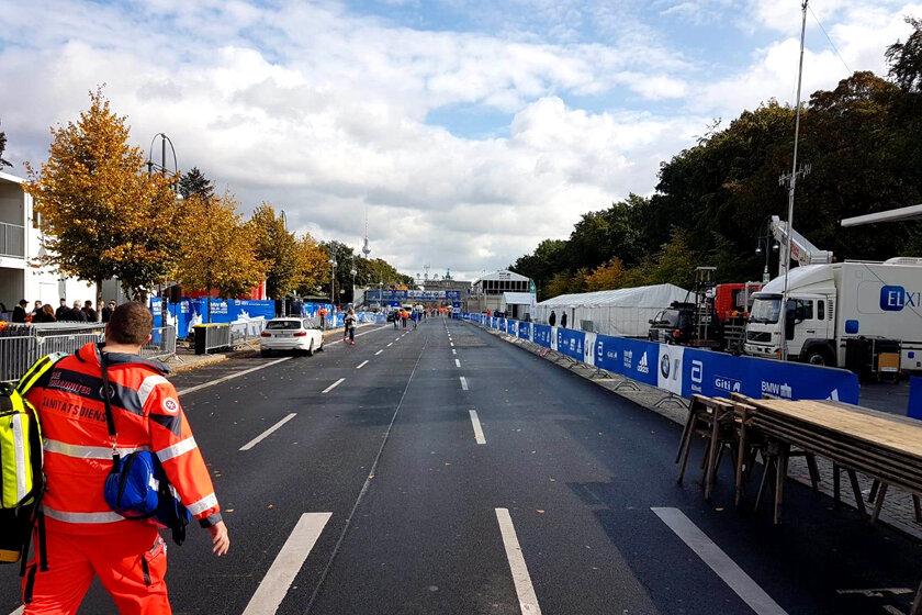 Mitarbeiter des Johanniter-Sanitätsdienstes im Vordergrund mit Blick auf die Laufstrecke in der Mitte Berlins.