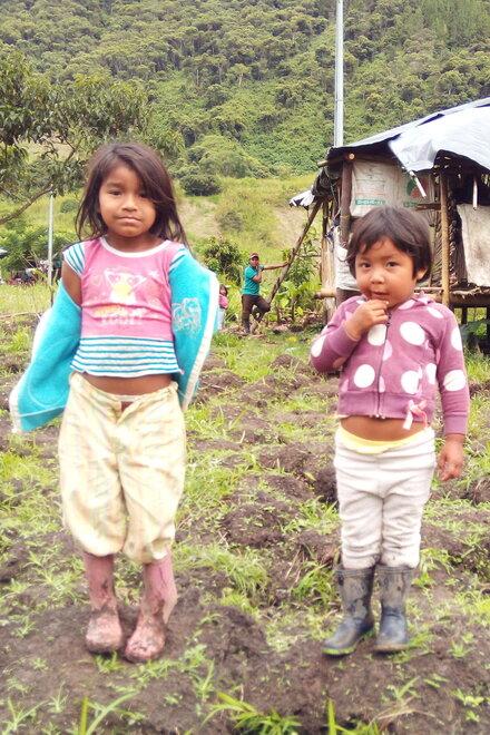Zwei kleine Mädchen stehen in schmutziger Kleidung auf einem Feld. Im Hintergrund ist eine Holzhütte
