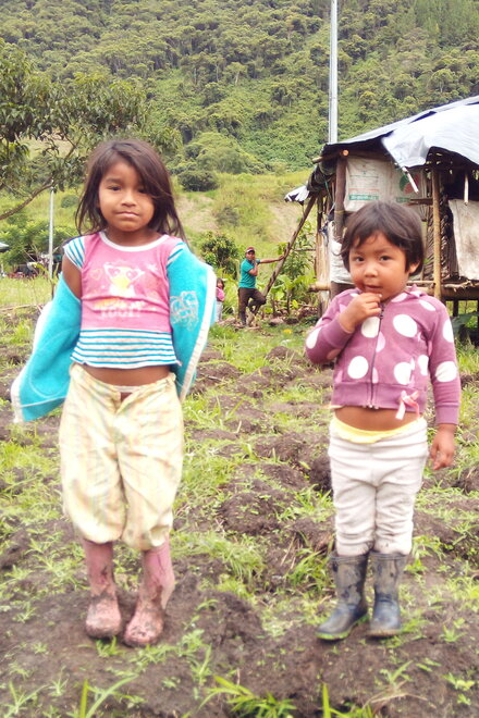 Two little girls are standing in a field in dirty clothes. In the background is a wooden hut