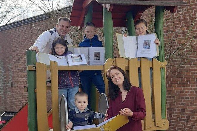 Familie Lies im stehen und sitzen im und am Kinderspielhaus