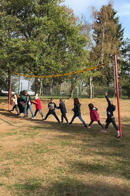 Kinder stehen in einer Reihe unter einem Volleyballnetz und spielen ein Spiel.