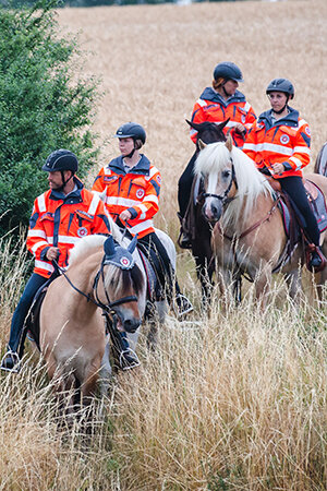 Eine Gruppe Sanitätsreiter der Reiterstaffel in unwegsamem Gelände.