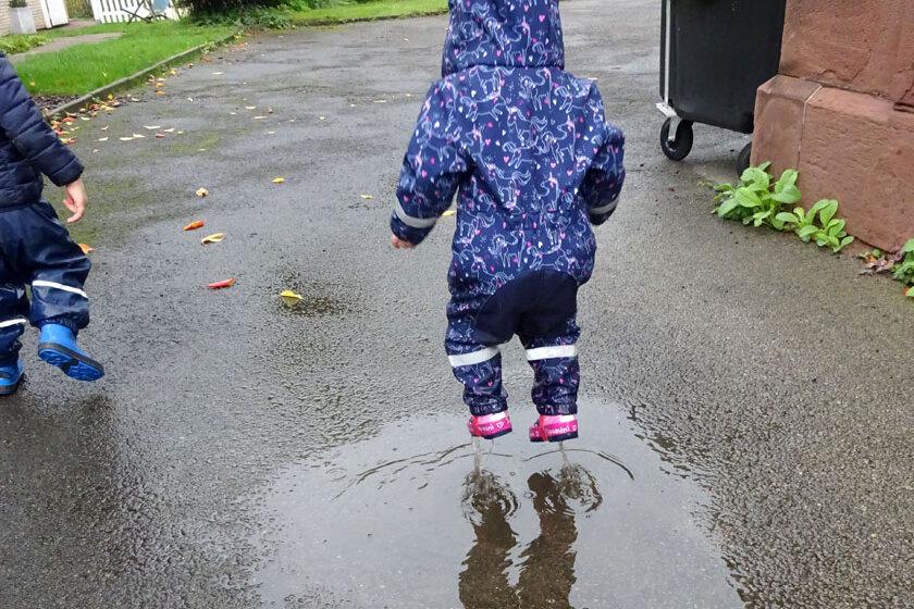 Kita-Kind springt mit Regenklamotten und Gummistiefeln in eine Pfütze.