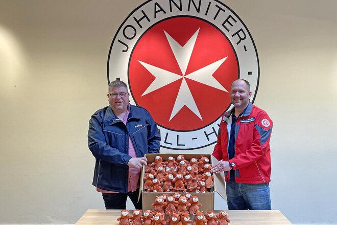 2 Männer mit einem Karton voller Stoffeichhörnchen vor dem Johanniter-Logo