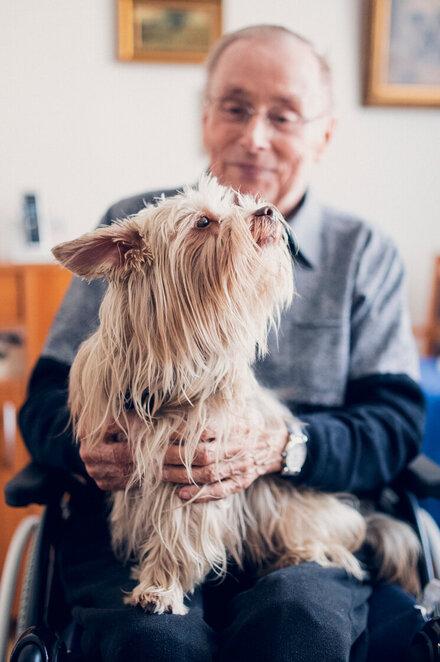 Bewohner im Rollstuhl hat einen kleinen Hund auf dem Schoß im Haus Lübeck
