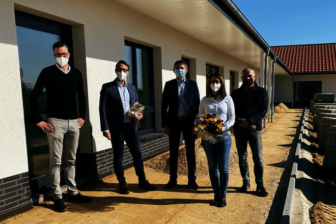 Vier Männer und eine Frau mit einem Blumenstrauß stehen vor einem weißverputzten Gebäude. Alle tragen medizinische Masken.