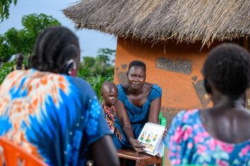 Amin klärt zwei Mütter mithilfe eines Plakats auf