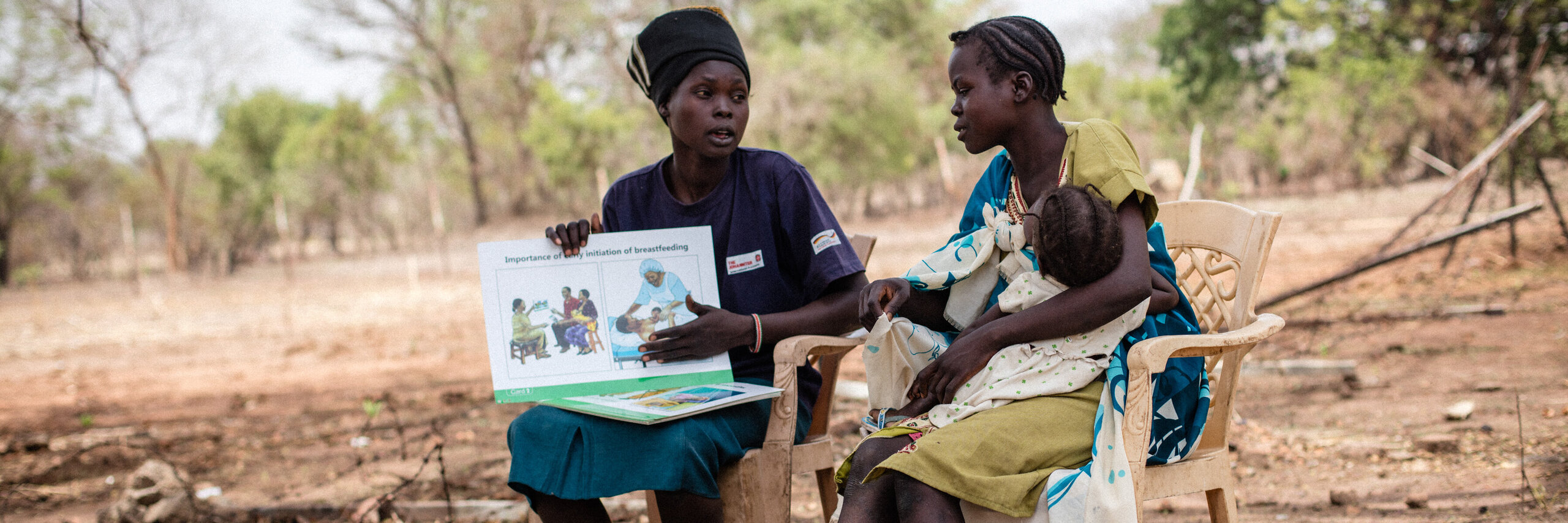 A mother explains to another mother with an infant the advantages of breastfeeding in a field.