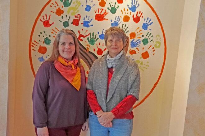 Tanja Gutknecht und Britta Thater-Mattke steht vor einen Zimmerwand mit bunten Handabdrücken.