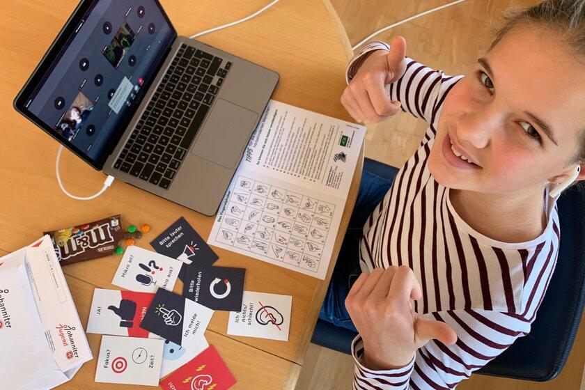 Ein Mädchen sitzt vor einem Computer, neben dem verschiedene ausgedruckte Zettel liegen. Sie guckt nach oben, lächelt und streckt beide Dauemn nach oben.