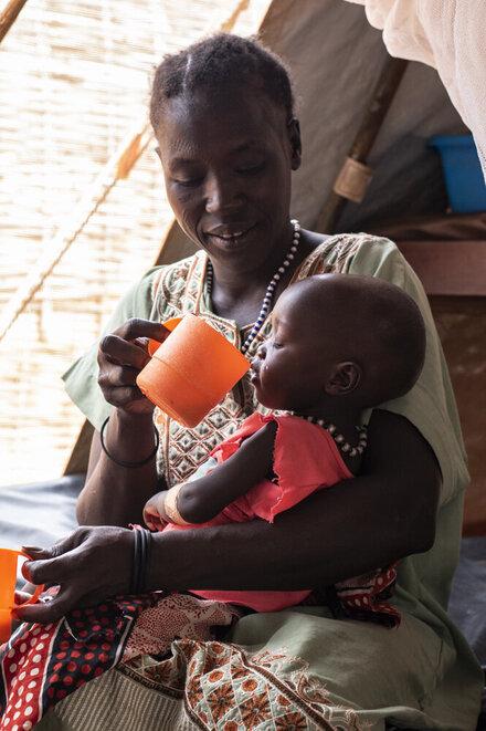 A women is feeding her child with a mug