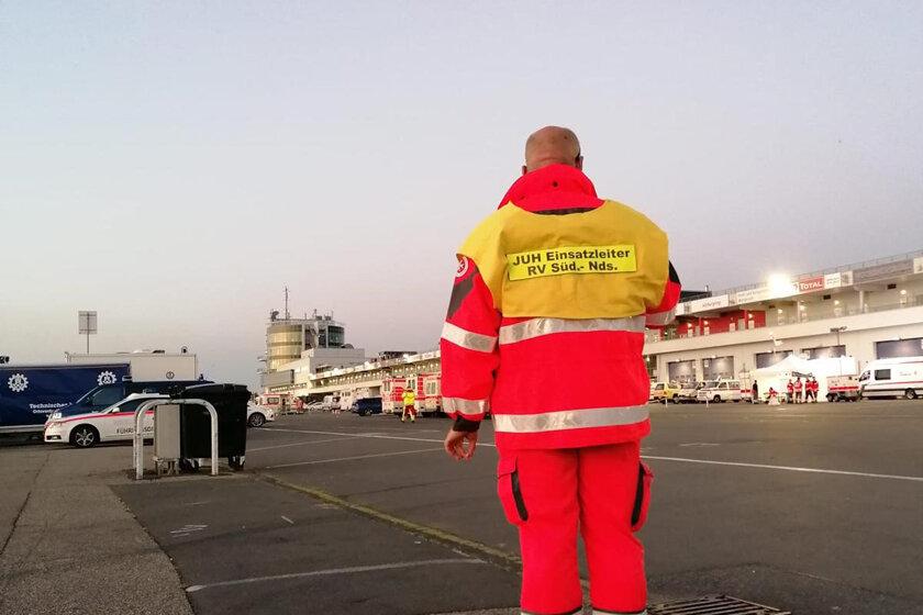 Regionalbereitschaftsführer Marc Küchemann mit Blick auf den Nürburgring und die dortigen Einsatzfahrzeuge sowie Helferinnen und Helfer.