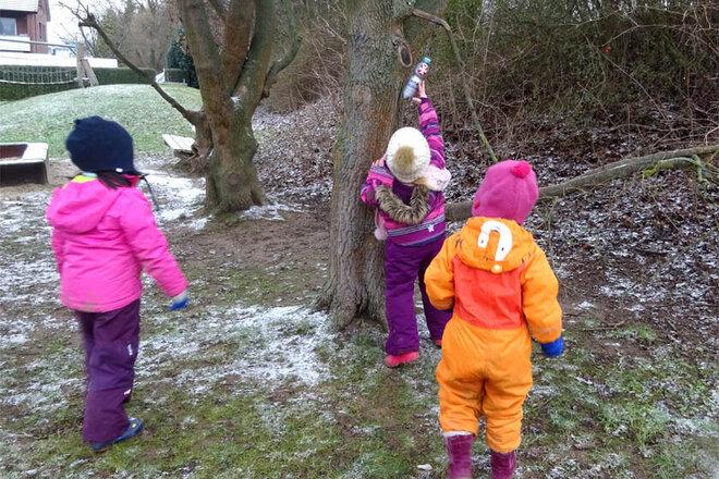 Kita-Kinder verstecken die Flaschenpost an einem Baum.
