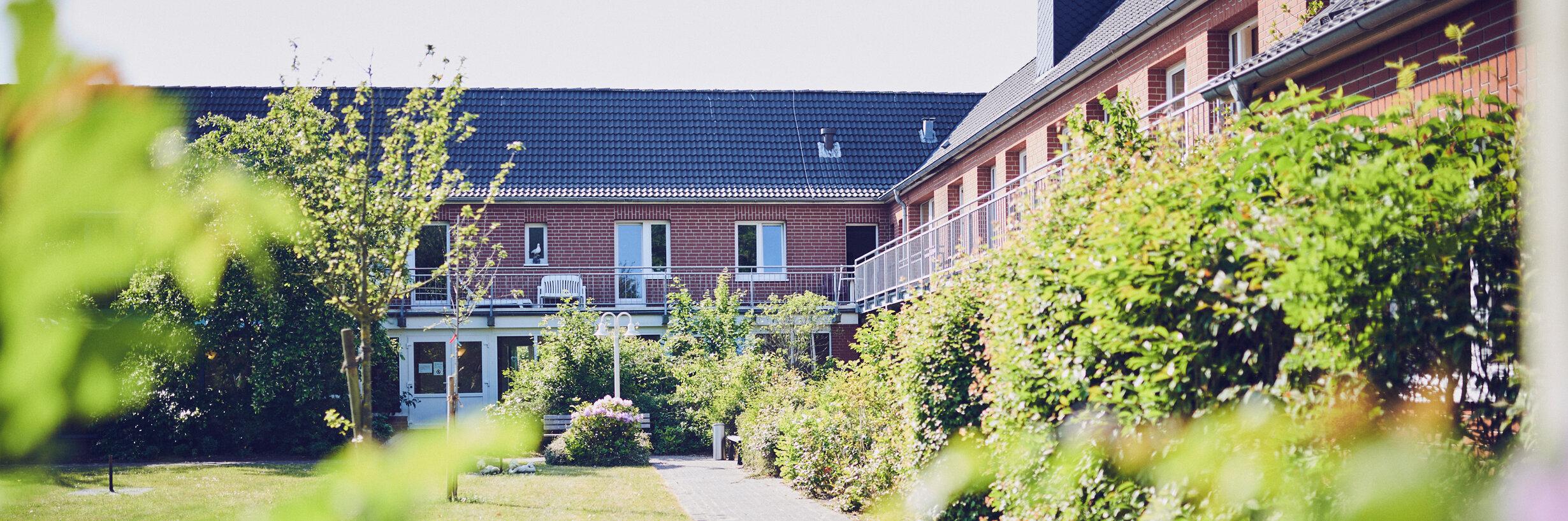 Sonniger Weg umgeben von Grünpflanzen und Rasen führen zum Senioren- und Pflegeheim