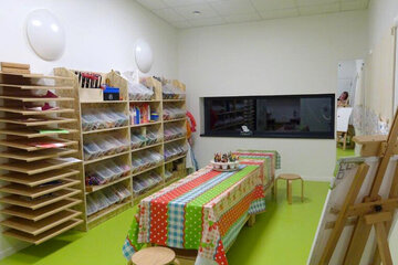 In der Mitte des Raumes ist ein Tisch mit einer bunten Wachstischdecke zum Basteln und Malen. An der Wand steht ein groeßen Regal mit vielen Schuladen in denen sich zahlreiche bunte Pappen und andere Bastelmaterialien befinden.