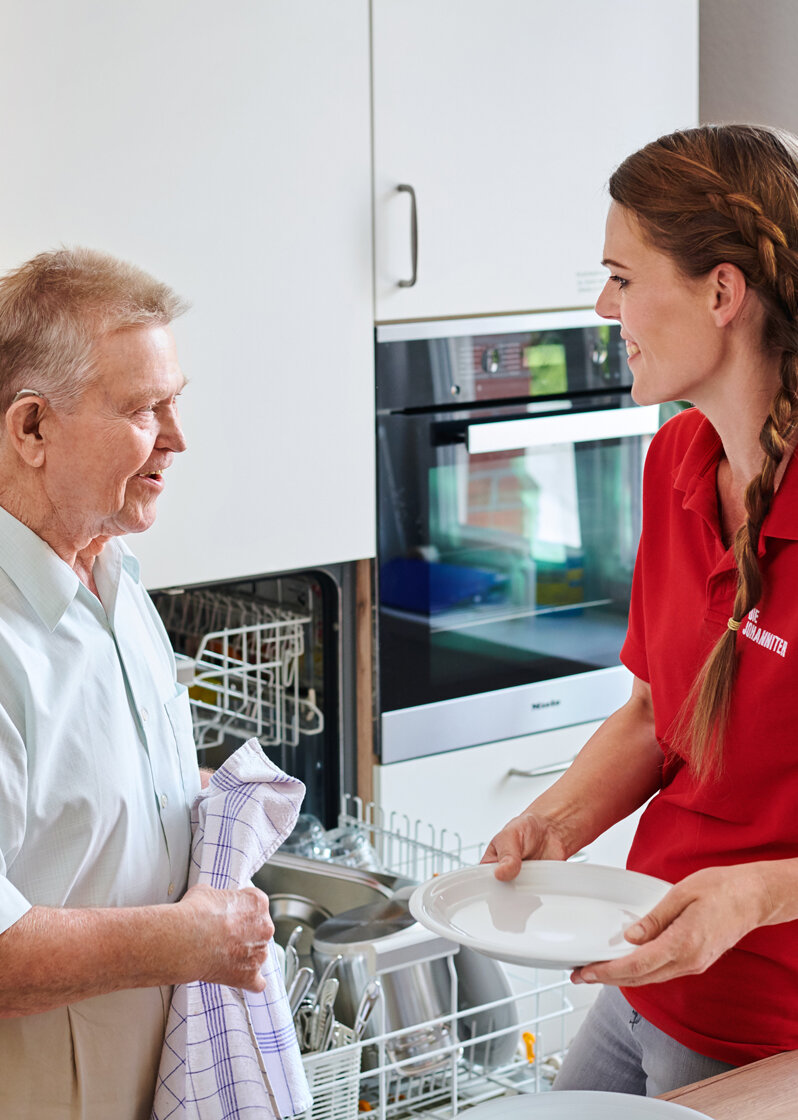 Eine junge Frau hilft einem älteren Mann beim Geschirrabtrocknen