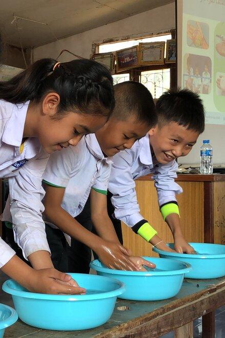 Vier Kinder waschen sich die Hände