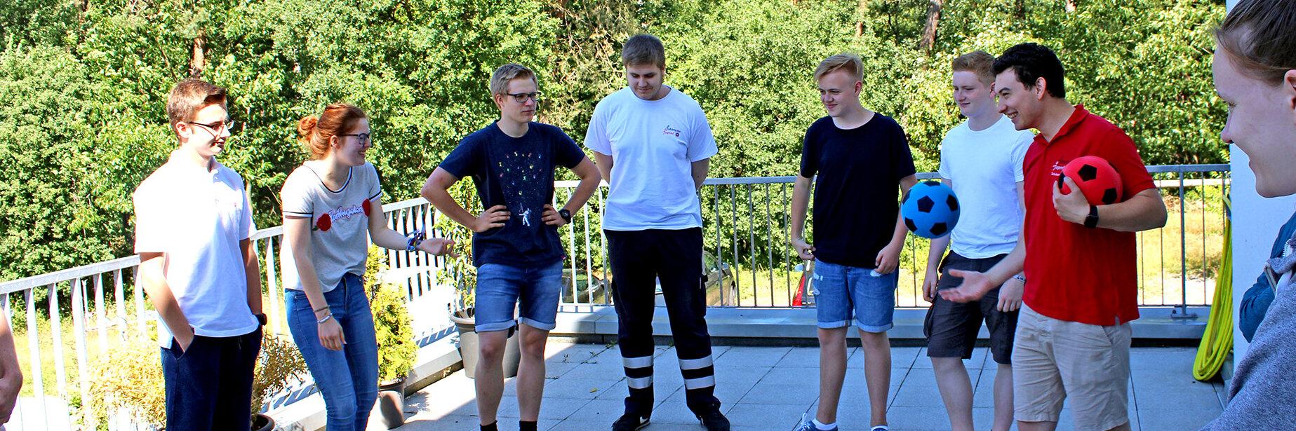 Jugendliche stehen in einem Halbkreis und spielen, von einem jungen Erwachsenen in Johanniter-Jugend-Polo geleitet, Ball.