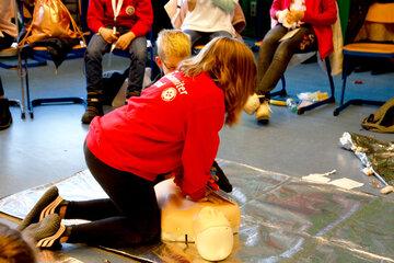 Ein Mädchen führt Herz-Lungen-Wiederbelebung an einem Dummy durch.