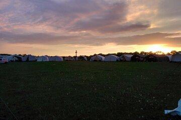 Eine Wiese beim Sonnenuntergang. Am Rand der Wiese stehen Zelte und es ist ein großes Kreuz im Gegenlicht zu sehen.