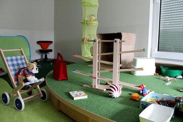 Kugelbahn, Kinderwagen und Kuscheltiere neben und auf dem Spielteppich im Gruppenraum.