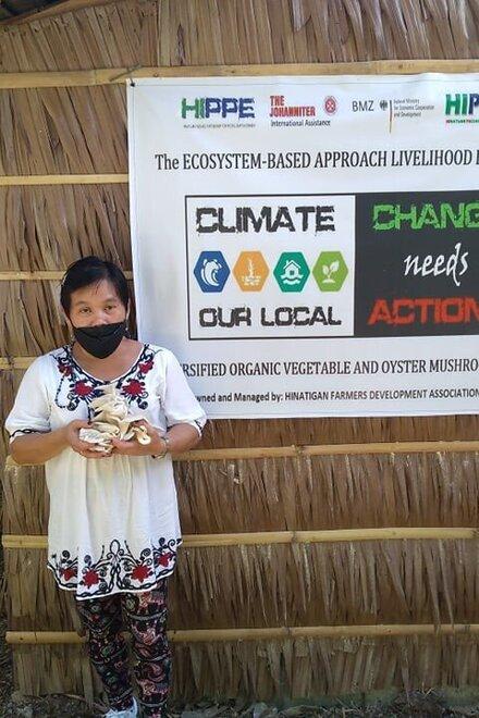 Ein Frau mit Mundschutz steht mit Pilzen in den Händen vor dem Projektbanner
