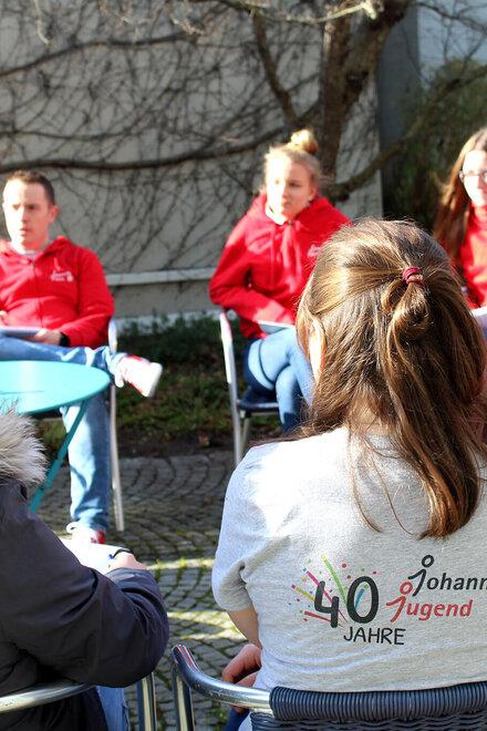 Eine Gruppe von jungen Menschen sitzt in einem Stuhlkreis und unterhält sich. Alle tragen Johanniter-Jugend-Kleidung.
