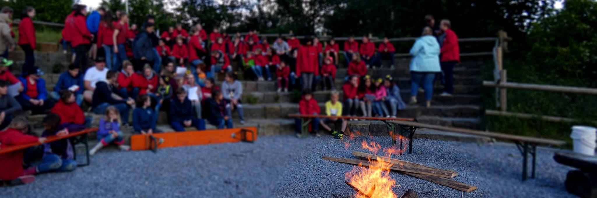 Johanniter-Jugendliche sitzen um ein Lagerfeuer