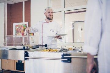 Ein Koch bei der Essensausgabe