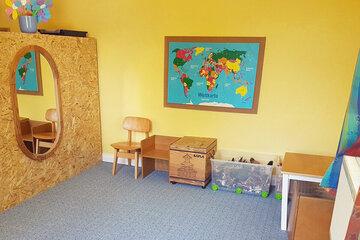 Landkarte an der Wand, Teppich zum Spielen und einige Spielsachen in den Schränken.