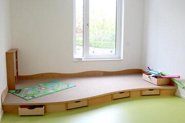 Spielecke mit grauem Teppich auf einer kleinen Erhöhung, darunter befinden sich Schubladen mit Spielsachen.