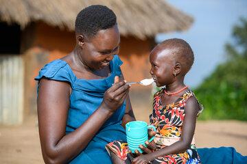 Amin füttert ihre Tochter mit Brei