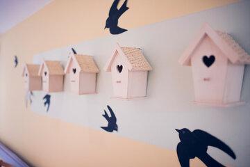 Ein Reihe kleiner Vogelhäuschen als Wandgestaltung