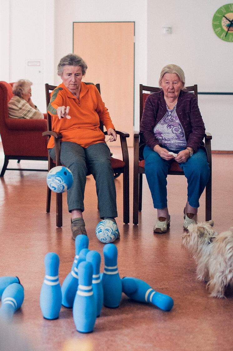 Zwei Seniorinnen kegeln im Sitzen auf dem Flur im Haus Lübeck