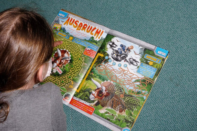 Ein Mädchen aus der Randschulbetreuung blättert in einer Zeitschrift und liegt dabei auf einem Teppich.